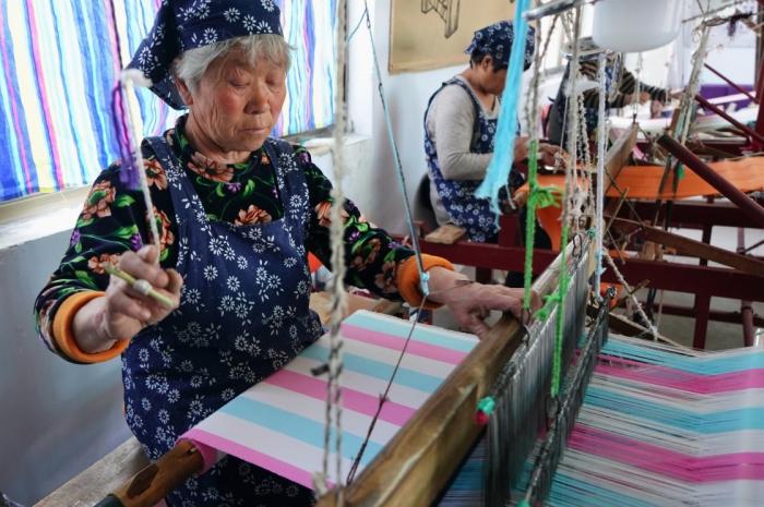 伝統的な織機で農村振興の曲を奏...